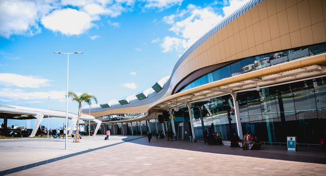 Faro, Portugal - May 3, 2018: Exterior view of Faro International Airport where passengers are walking with their suitcases on a spring day
