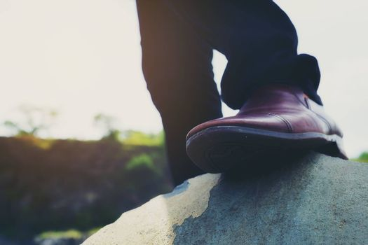 Photo of hipster men's fashion shoes in brown suede shoes walking on rocks in bright weather.