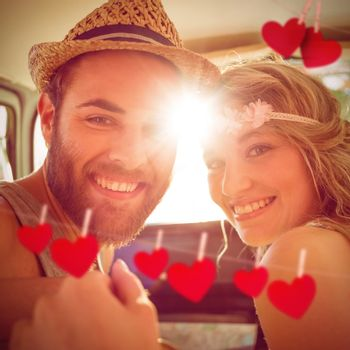 Hipster couple on road trip against hearts hanging on a line