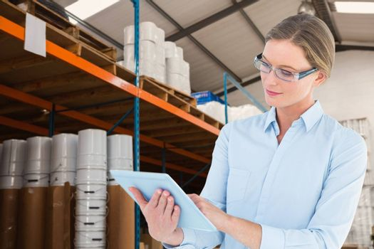 Businesswoman using tablet pc  against warehouse manager checking her list on clipboard