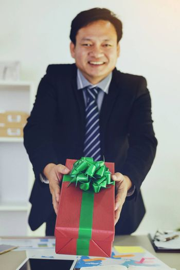 Executives give boxes to the staff and smile happily.