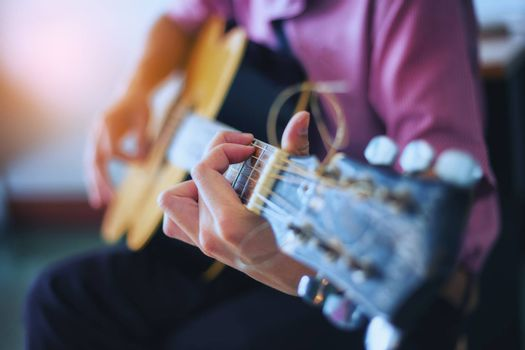 The musician is enjoying the guitar. Focus on fingers
