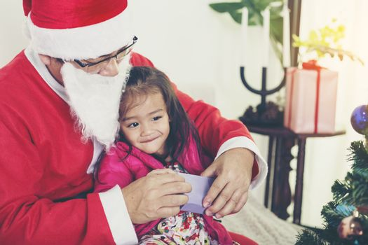 Santa Claus gives gifts to girls and boys during the Christmas season.