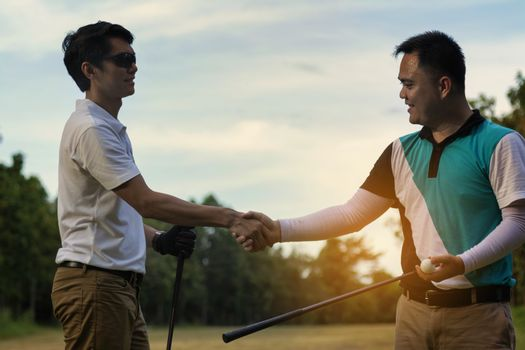 Young handsome businessman shake hands on the golf course and negotiate business casual.