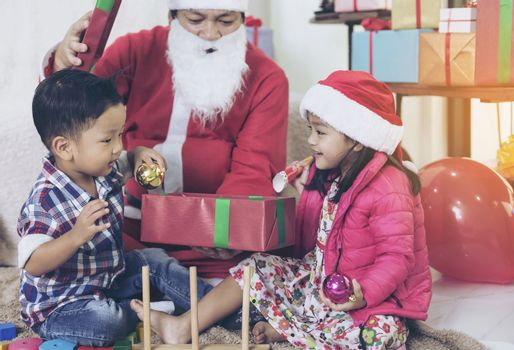 Santa Claus gives gifts and reads fairy tales to boys and girls listening in the festive season.
