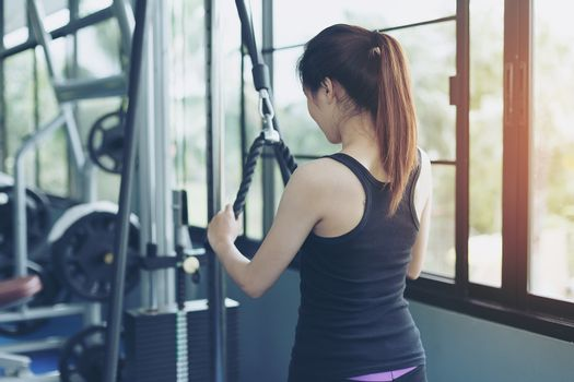 Beautiful girl exercises by pulling the rope to strengthen the muscles in the public gym. Strength training of the arm muscles. Health care concept