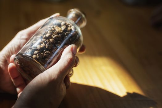 Close-up image of hand holding coffee beans in glass bottles