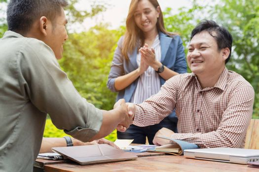 Young business men are negotiating with customers. And shake hands after the negotiations.