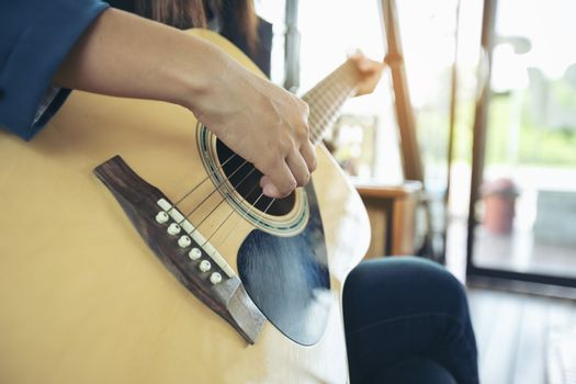 Beautiful girl is playing guitar by the window. Education lifestyle relax concept
