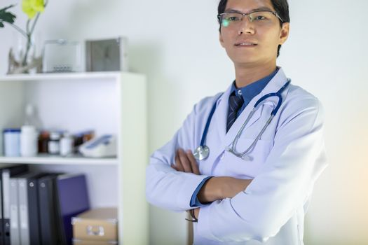 Portrait of doctor standing in his private clinic. Medical physician doctor man over clinic background. Doctor.