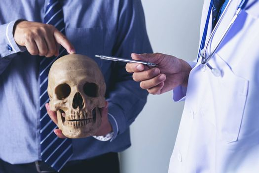 Doctor is holding a human skull in his hands and point to the skull for teaching and diagnose the symptom to the intern and medical students.