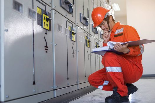 A handsome electrician is checking the electrical equipment to prepare it for use.