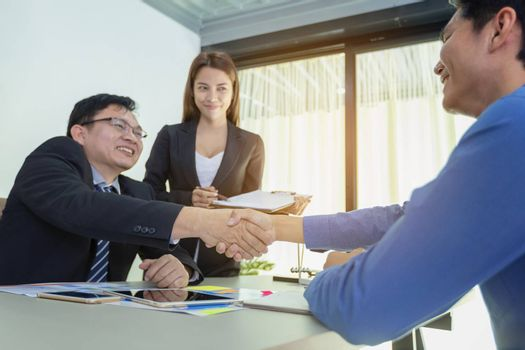 Business people handshake, businessmen hand shake, during meeting signing agreement sitting at desk team work group on conference discussing financial diagram, graph, business charts