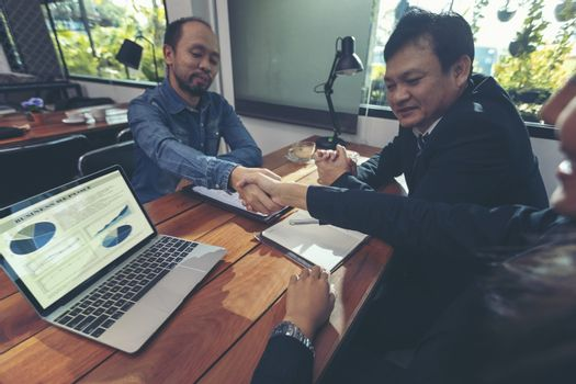 Happy smiling businessmen handshaking after signing contract mee