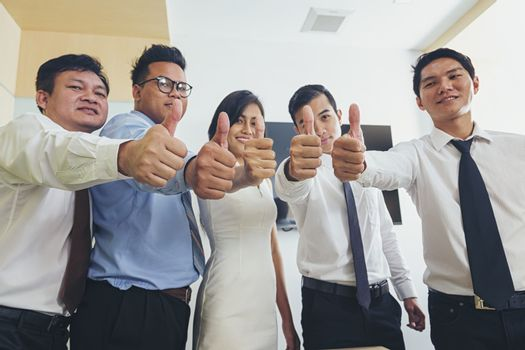 Successful business negotiators show thumbs up and smile happily.