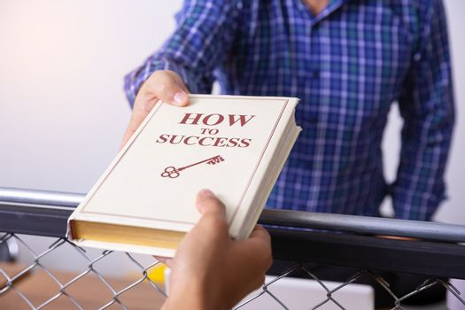 Senior businessman deliver the book about the keys to business s