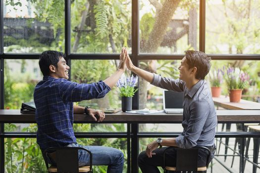 Businessmen negotiate in a coffee shop. Hold hands and greet bef