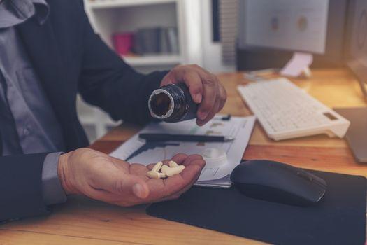 Stressed businessman having severe headache, holding painkiller
