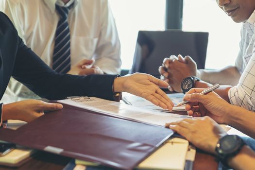 Businessmen negotiate and sign contracts. They are pointing to documents and discussing businessmen and customers. DEAL agreement Working together, talking in the office concept.