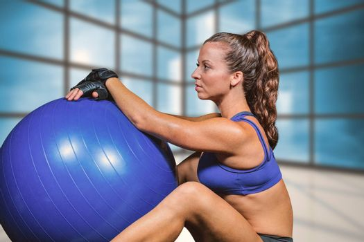 Side view of sporty woman with exercise ball against cityscape seen through window