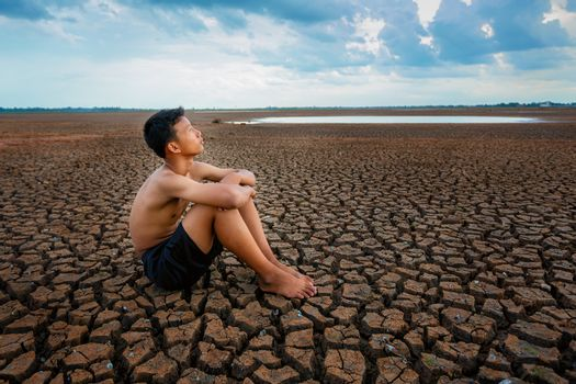 Sad a boy sitting on cracked earth waiting for the hope of the sky to rain. Affected of global warming made climate change. Water shortage and drought concept.