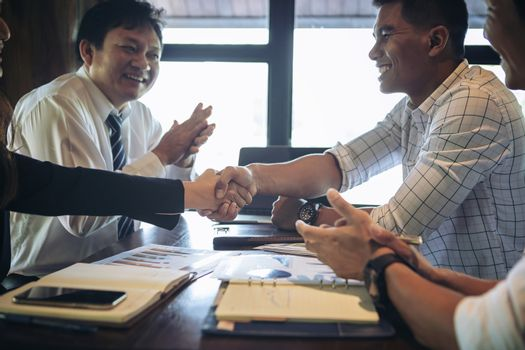 Two business teams successfully negotiating, shaking hands. At meeting table business groups shaking hands on completed deal. handshake on the background of applause