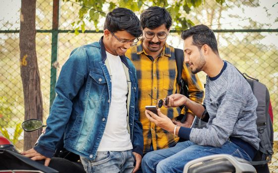 Students busy on mobile at college parking area on bike - Young millennials busy on phones and technology - concept of friendship and urban youthful lifestyle.