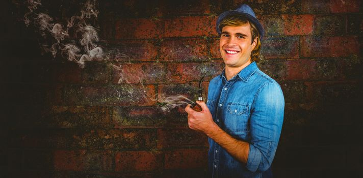 Cheerful hipster holding pipe against texture of bricks wall