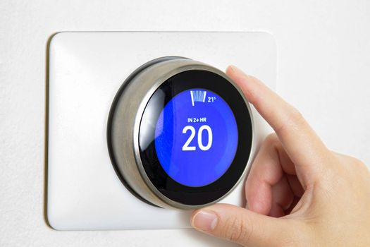 A person cooling down Home Air Conditioning, temperature is on centigrade celsius metrics using a smart thermostat on a white wall.