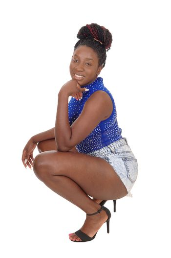 A beautiful African American woman in a blue top and shorts  crouching on the floor, smiling, isolated for white background