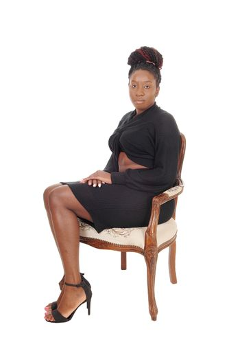 A gorgeous African American woman in a long gray dress sitting in an old armchair, isolated for white background