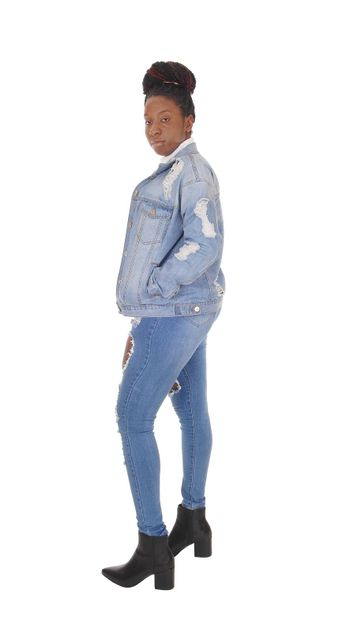 A young African American woman standing in ripped jeans and a jacket and white top, isolated for white background