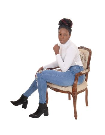 A young serious looking African American woman sitting in an old armchair in jeans and white top, isolated for white background