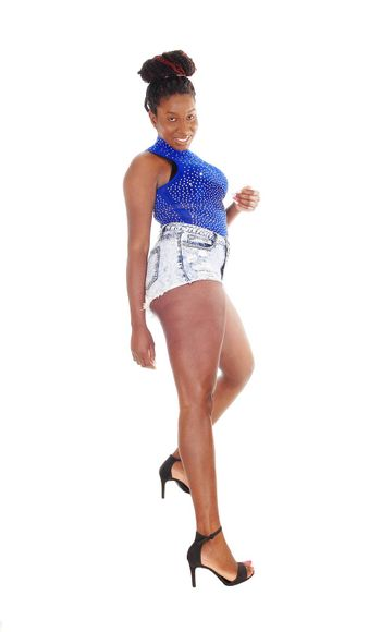 A tall young African American woman standing in jeans short and a blue top in profile isolated for white background