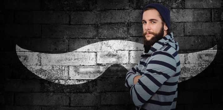Portrait of confident hipster with hooded shirt against texture of bricks wall