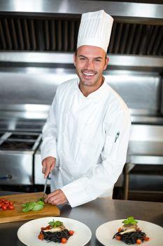 Handsome chef slicing garnish