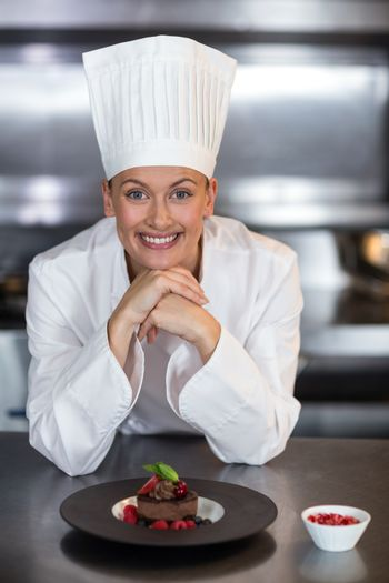 Portrait of happy female chef with hands on chin