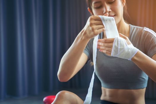 Beautiful women who love health. Two of her hands with white boxing bandage hand wrap to prepare for exercise by boxing. Active girl fight