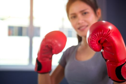 Woman with red boxing wraps and boxing gloves on hands boxing in ring. Active girl fight