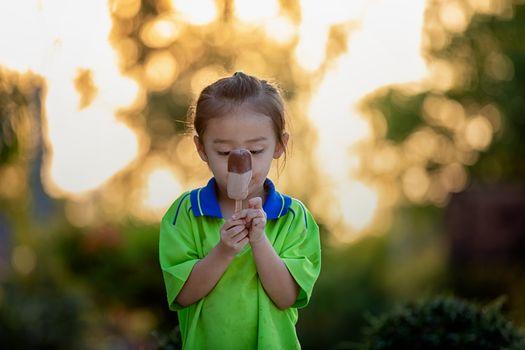 portrait of happy girl eats ice cream in a public garden.