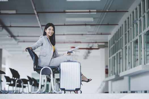 Portrait of business woman looking digital tablet with white travel bag While waiting to travel to the destination