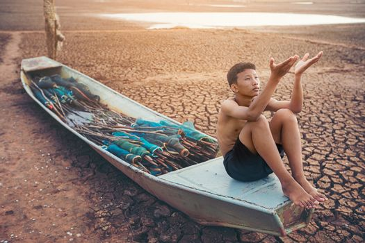 Sad a boy sitting on a boat that was parked in an arid ground fo