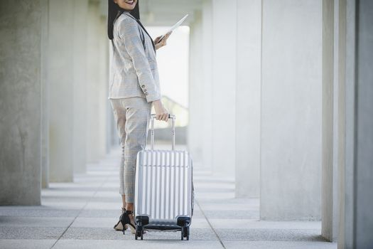 Portrait of business woman looking digital tablet with white travel bag on walkway while waiting to travel to the destination