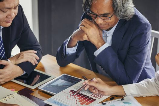 Image of business people hands working with papers at meeting. Businessman holding pens and holding graph paper are meeting to plan sales to meet targets set in next year.