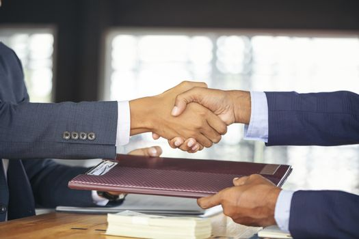 Young business people shaking hands in the office. Finishing successful meeting. Businessman holding pens and holding graph paper are meeting to plan sales to meet targets set in next year.