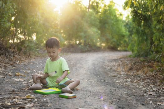 Asian children sit and draw on a drawing board in the midst of beautiful nature at sunset.