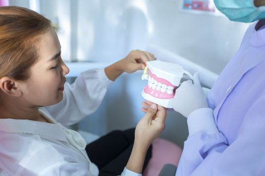 The dentist is demonstrating how to brush teeth for the patients sitting on the dental chair in her clinic.