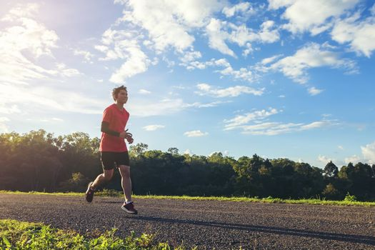 Handsome young man runs for good health on a rural road that is full of forests and beautiful nature.