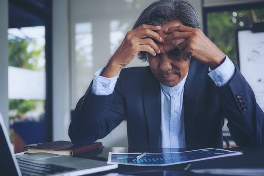 Pictures of serious business executives with information placed on the desk to make business investment decisions.