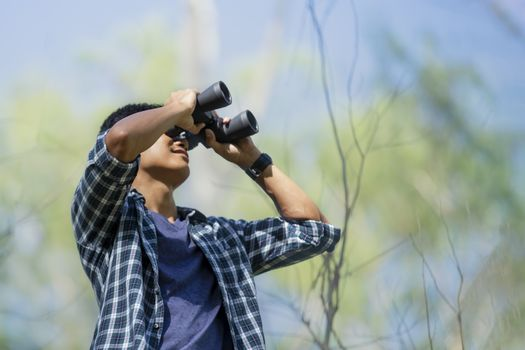 Close-up of Asian handsome man holding / looking / watching using binoculars with copyspace